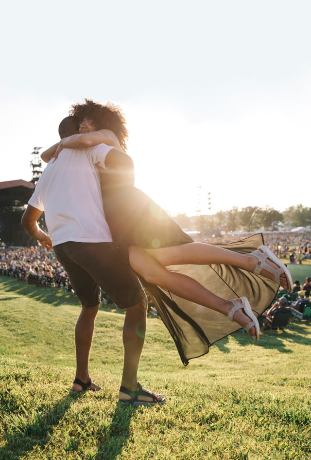 Man, wearing Teva's, lifts woman up, who is also wearing Teva's.
