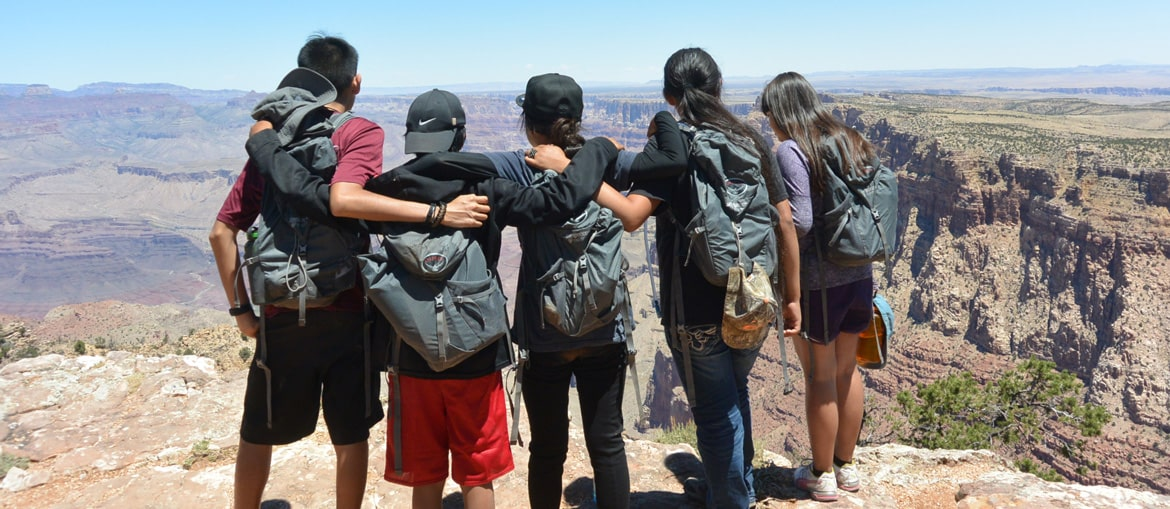 Picture of people standing in front of the Grand Canyon.