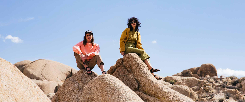 People sitting on rocks wearing Teva shoes.